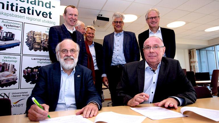 Rektor Petter Aasen og Yaras Ole-Jacob SIljan signerer avtalen og smiler til kamera. De andre står bak som vitner.