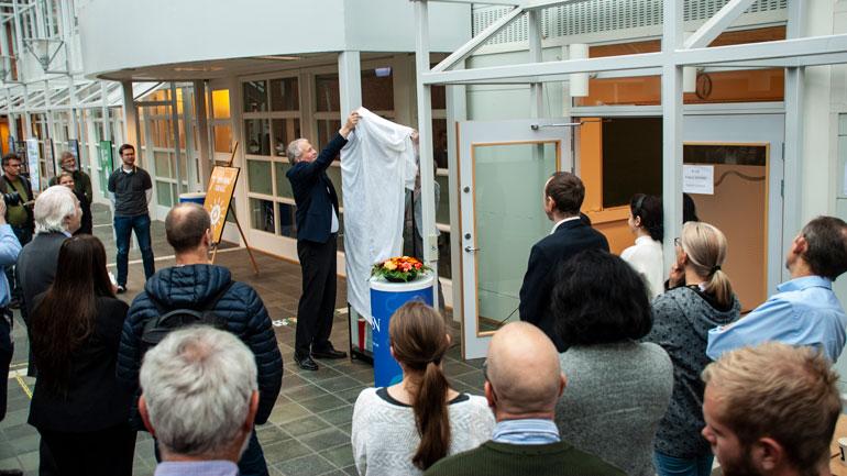 Dekan Morten Melaasen avduker glassmonteren med alle hundre disputasene, og alle gjestene står og ser på.