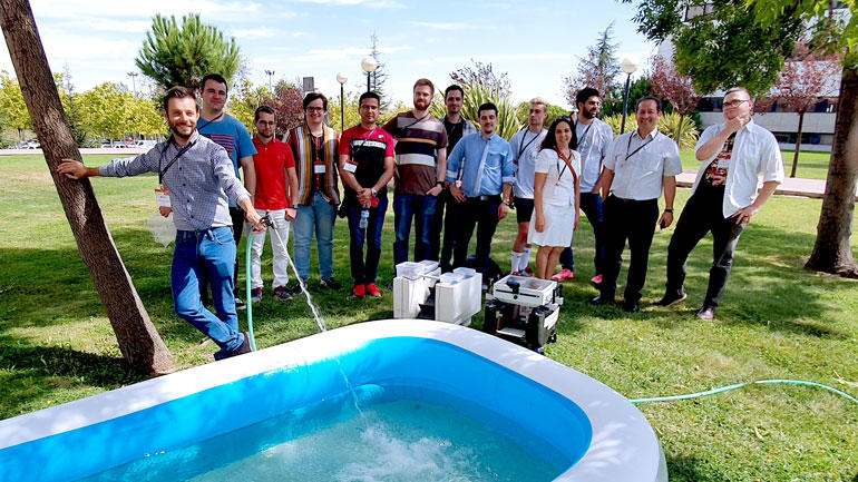 Ingeniørstudenene fra USN og det spanse laget står oppstilt foran et plastbasseng hvor roboten skal testes.