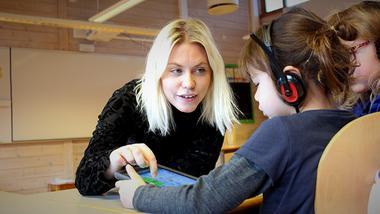Lærerstudent Vanessa Sunnset underviser skoleelev om noe på nettbrett. foto.
