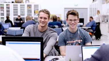 To studenter på elektroingeniør smiler til kamera.