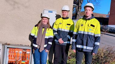 Masterstudentene Vilde Sundling, Simen Torvund Sørlie og Odin Dahle Sjåstad står ved et kabelskap og smiler til kamera.