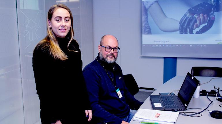 Student Hanna Borch og prosjektleder Lars-Cyril Blystad foran bilde av armprotesen og ser rett i kamera