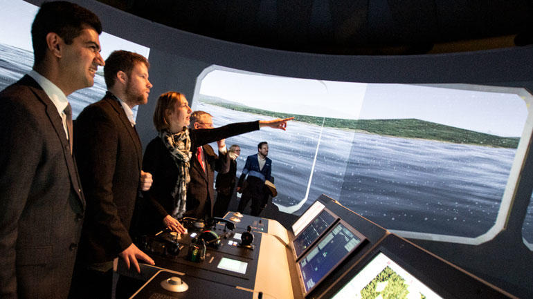 Statsråd Iselin Nybø tar styringen på det maritime simulatorlaboratorium på USN. Til venstre professor Salman Nazir og bachelorstudent i nautiske operasjoner, Adrian Andersen.
