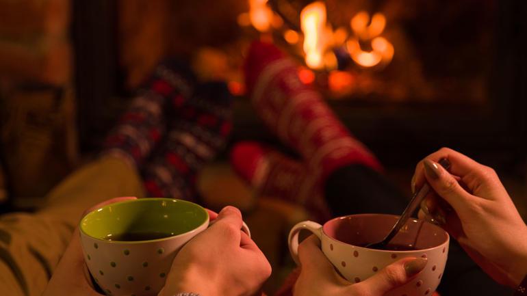 Par som holder kopper foran peisen i julen.  Foto
