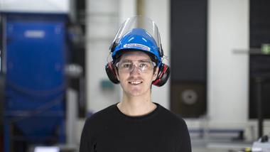 En mannlig ingeniørstudent med hørselvern smiler og ser rett i kamera