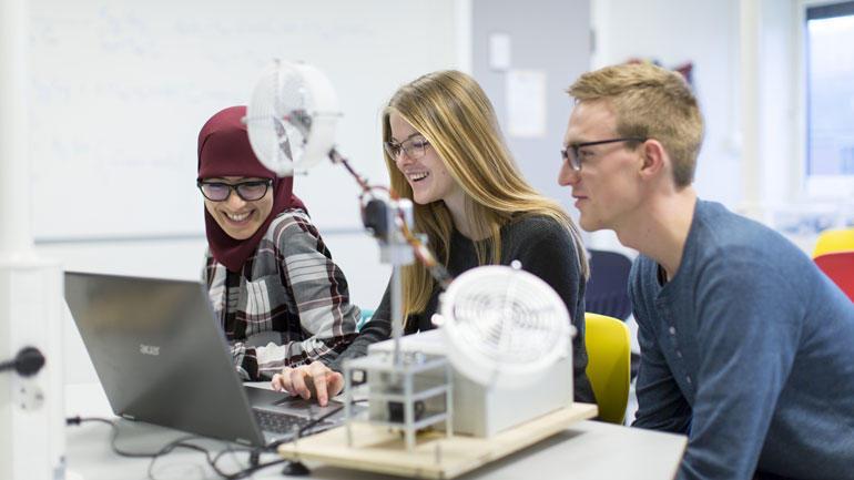 Tre ingeniørstudenter sitter ved pulten og jobber på et prosjekt.