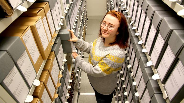 Caroline Klavenes jobber med Porsgrunds Porselænsfabrik-arkivet som avslutning på bachelor-oppgaven ved USN. Foto av henne i arkivet.