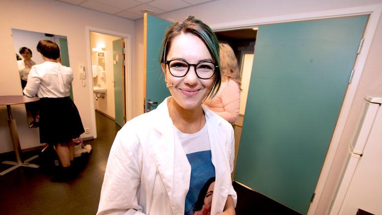 Selda Ekiz ser rett i kamera i garderoben, smiler og har på forkserfrakk rett froan fysikkshow i Bakkenteigensalen.