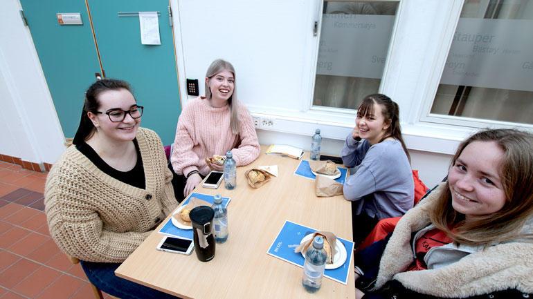 Fire jenter fra Lier videregående skole sittende rundt et bord mens spiser bagett og smiler.