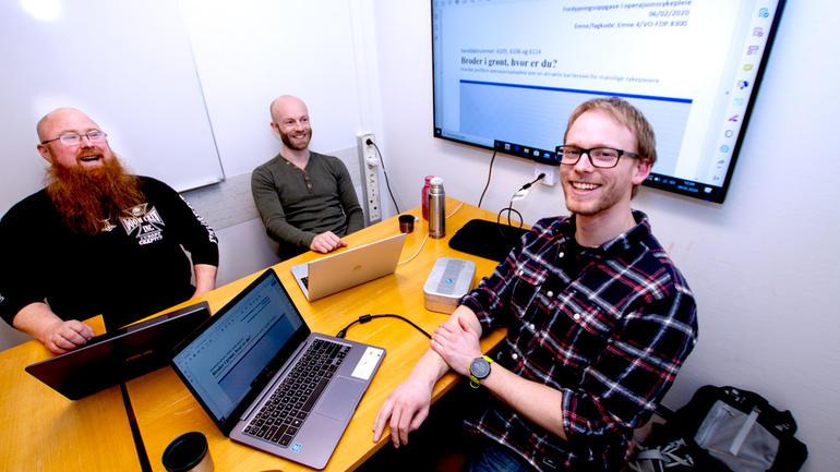 Operasjonssykepleiestudentene Bjørn Erik, Åsmund og Aleksander samlet rundt bordet i grupperom med TV på veggen hvor forsiden på oppgaven deres vises.