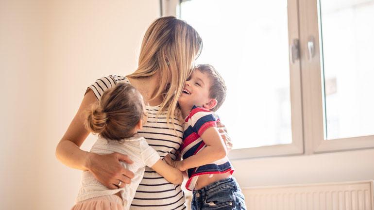 kvinne som omfavner to barn. Foto