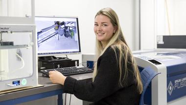 Dataingeniørstudent jente sitter foran data og snur seg mot kamera. Illustrasjon