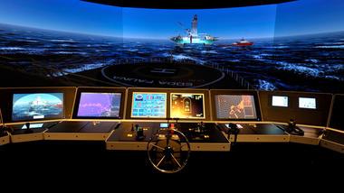 Maritim simulator illustrasjon som viser 360 graders skjerm med skip og oljerigg utpå havet og mange små dataskjermer og tastatur og ratt.