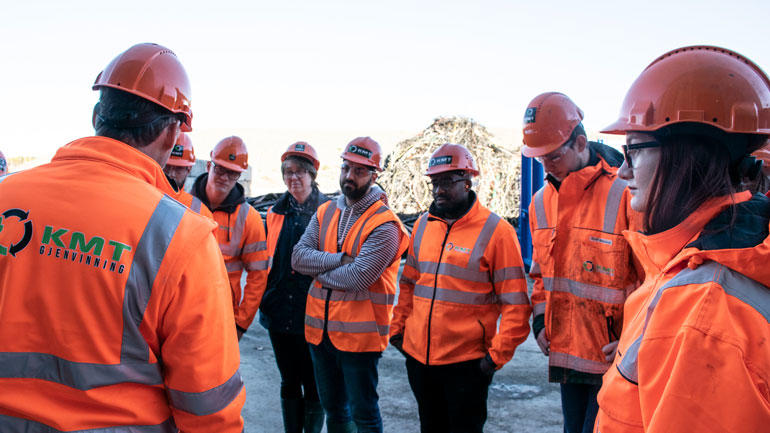 Ingeniører i oransje arbeidstøy og med oransje hjelmer på hodet står på en rekke på en industriplass og hører på en mannlig ingeniør som snakker. Illustrasjonsbilde