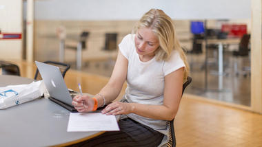 Kvinnelig student sitter og jobber alene foran laptop og skriver på et ark ved siden av.
