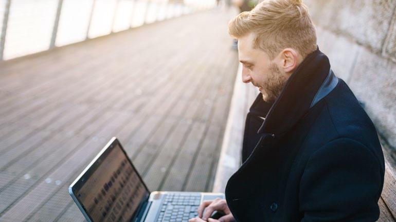 Mann sitter utendørs på en benk og jobber på laptopen.