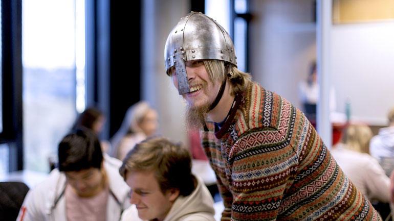 Mannlig lektorstudent i historie står i et klasserom i en undervisningssituasjon med en vikinghjelp hode og smiler til kamera.
