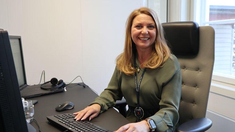Laura sitter på kontoret i kontorstol foran PC med hnedene på tastaturet og smiler til kamera