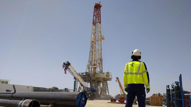Illustrasjonsbilde av et boretårn i Dubai med Kelda Drilling Controls og der en ingeniør i gul refleksjakke som står med ryggen til og ser på