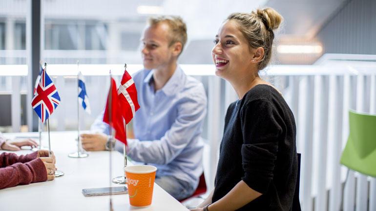 Gruppearbeid med en kvinnelig og mannlig student ved et bord med flagg fra Danmark og UK. Illustrasjon.