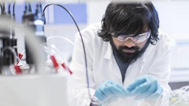 En mørkhåret student i hvit forskerfrakk og blå plasthansker jobber konsentrert i lab.