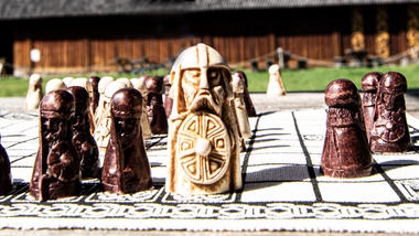 Brikker fra spillet hnefatafl plassert foran Gildehallen ved Borre Midgardsenter