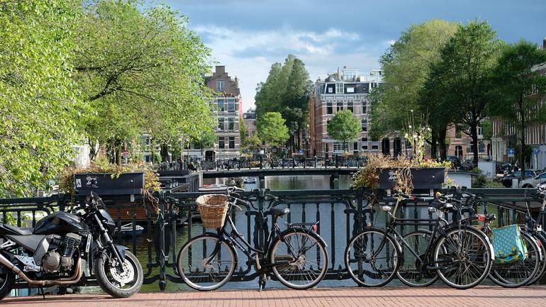 Fire sykler står på en bro i Amsterdam