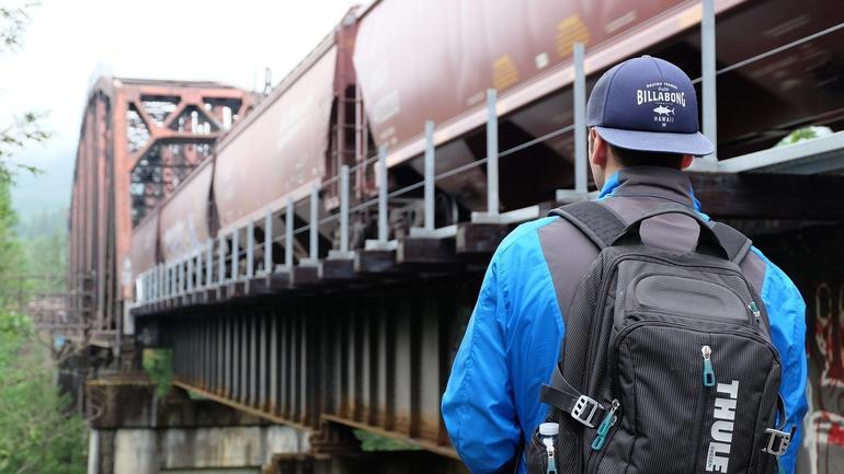 Ung mann med sekk på rydden, ser på togskinner