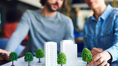 Personer med modeller av bygninger og trær. Foto iStock/gpointstudio