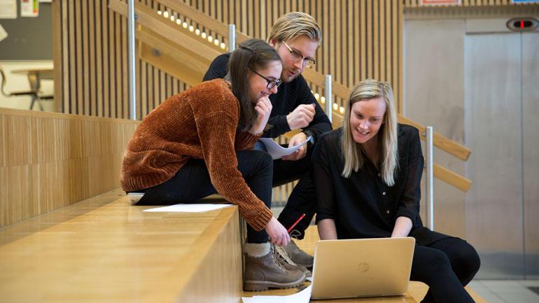 Studenter som sitter i trappa og jobber