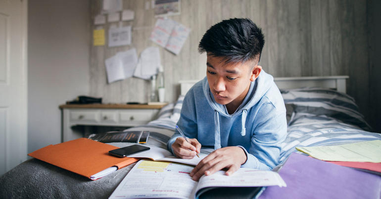 A young boy does schoolwork - iStock-SolStock