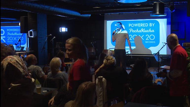 ein mann står i på scena foran publikum på Stasjonen i Tønsberg opplyst i eit lysskin som skriv Powered by PechaKucha på lerretet bak han.
