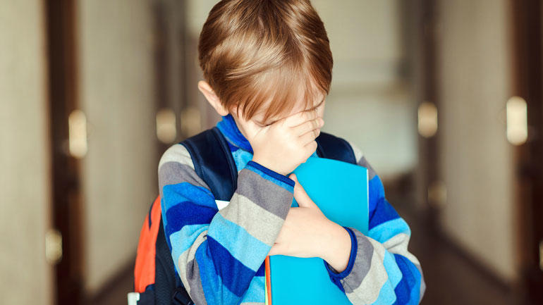 School boy hides his face
