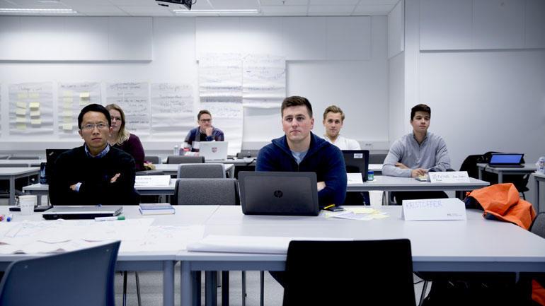 Studenter sitter foran laptoper på pulter i undervisningsrom.