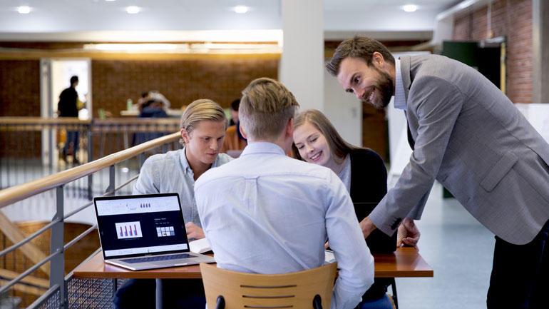 Gruppe med studenter som sitter og står rundt et bord og arbeider med laptop.