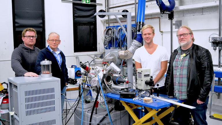 André Vagner Gaathaug, Dag Bjerketvedt, Joachim Lundberg og Knut Vågsæther står oppstilt foran teknisk system i lab.