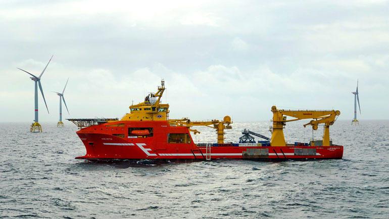 ødt tankskip ute på havet omringet av vindmøller/havvind