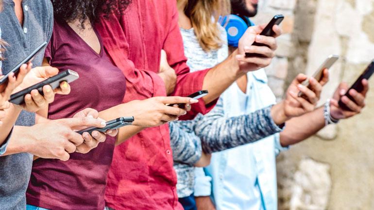 anonymiserte ungdommer med mobiltelefoner i hendene.Foto
