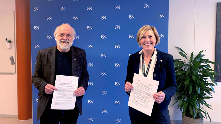 Rektor Petter Aasen og fylkesrådmann Lisbeth Eek Svensson står oppstilt med avtalen i hånda og smiler til kamera foran blå USN-vegg.
