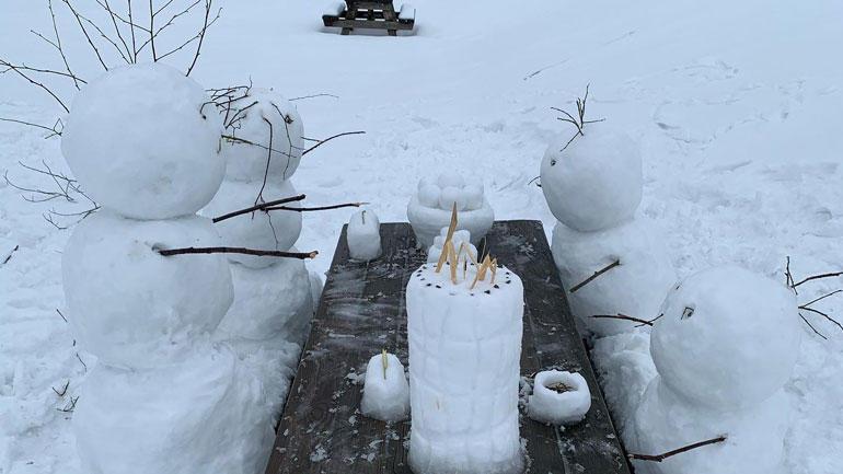 Bilde av fire snømenn som sitter på en benk