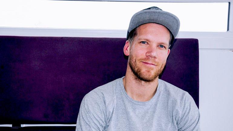 Lars Grorud i sivilt med caps og grå genser sittende i en lilla sofa. Portrett. Ser rett i kamera.