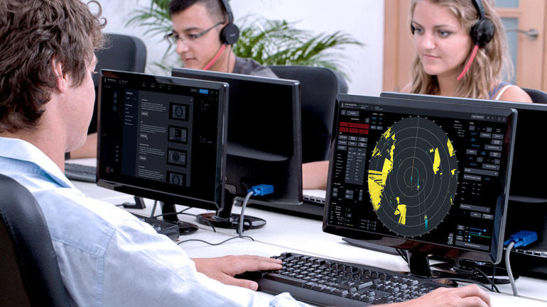 Studenter jente og to gutter i klasserom foran PC-skjermer med skybasert simulatortrening