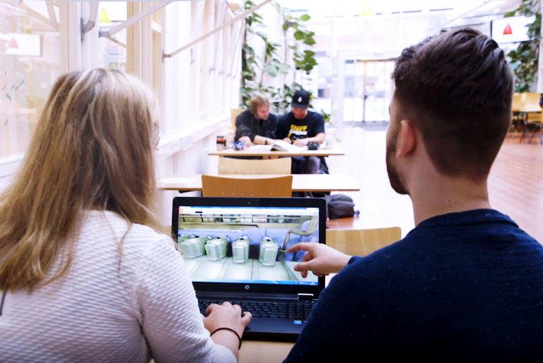 En jente og gutt studenter sittende med ryggen til foran en laptop på et bord i åpent universitetslandskap.