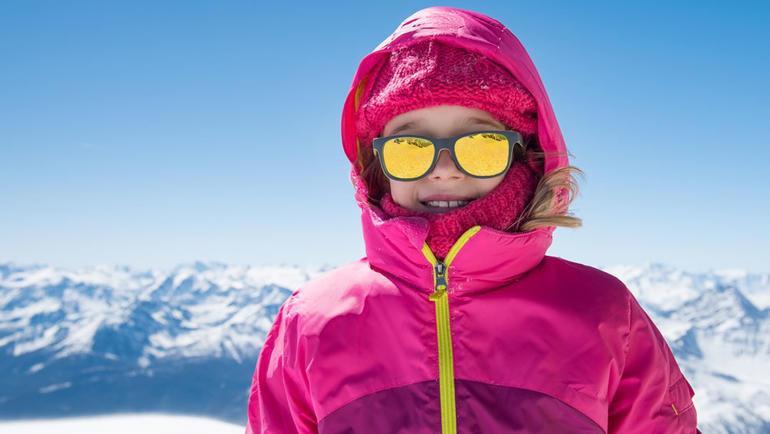 vinterkledt jente med solbriller. fjellandskap i bakgrunnen