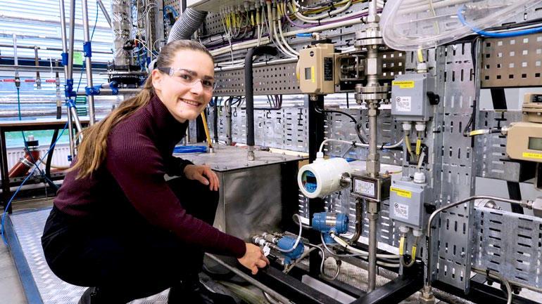 Emmy sitter på kne foran utstyr i prosessanlegg og smiler til kamera