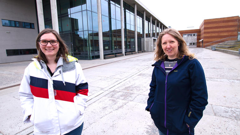 Hanna og Karina står utenfor i\hovedinngang til campus Vestfold og smiler til kamera.