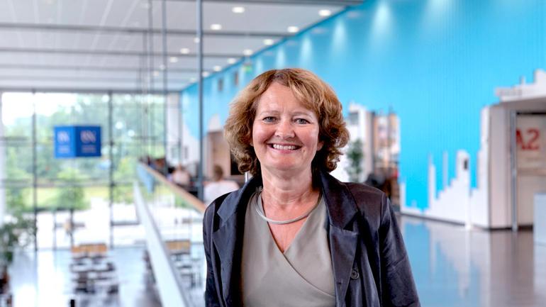 Portrett av Ingvild Marheim Larsen innendør på campus smilende til kamera.