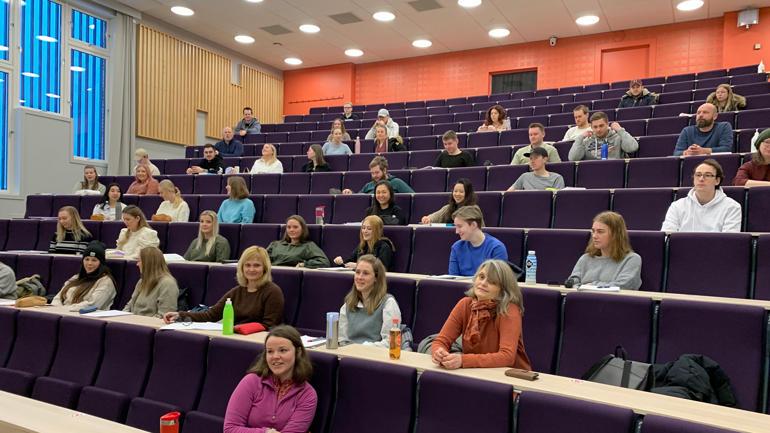 Studenter i forelesningssal med koronaavstand.