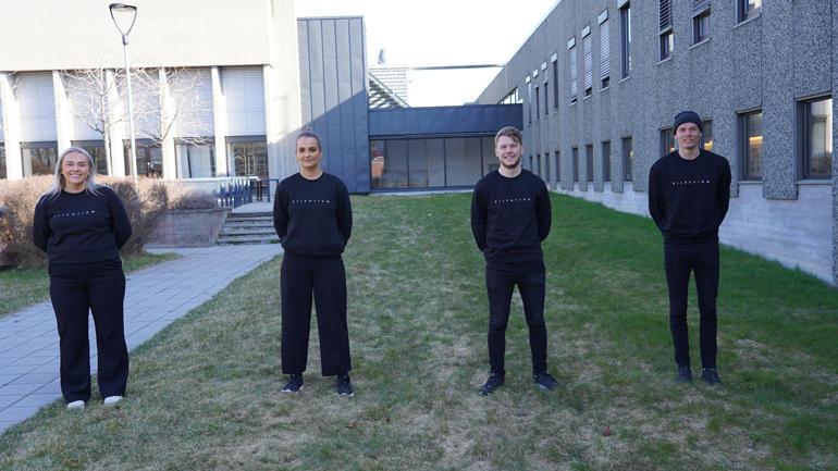 Teamet i Silentium står på rekke i sorte klær utendørs og ser i kamera. Helfigur.